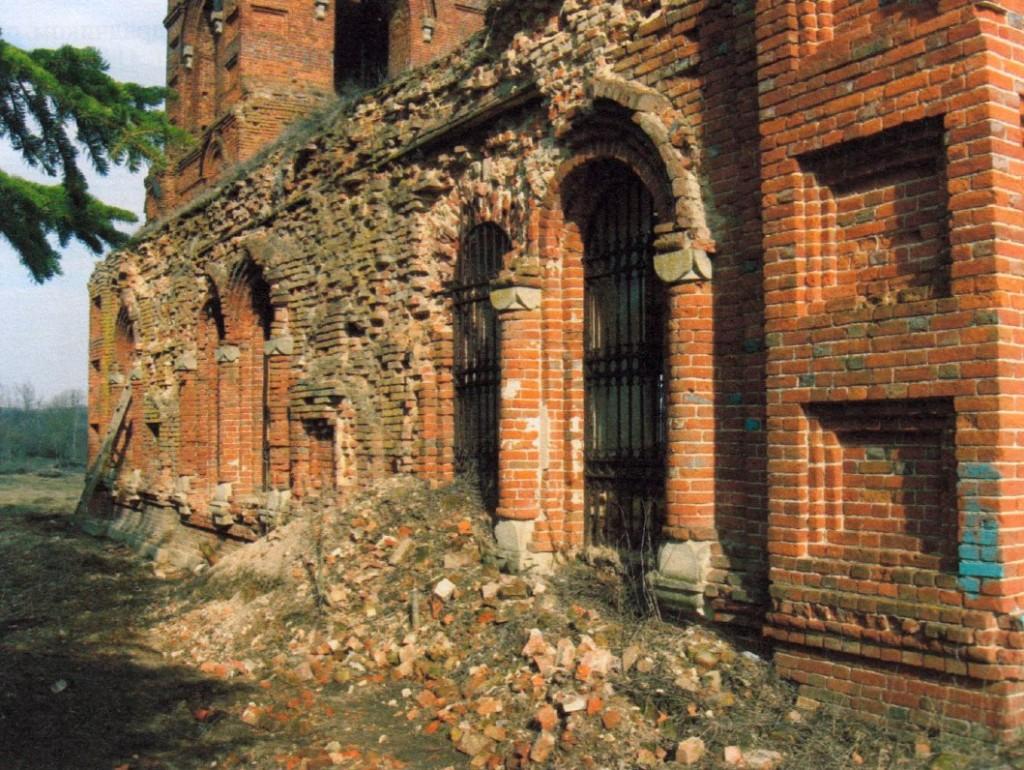Фото 2. Общий вид южного фасада трапезной. В восточной части фасада цоколь завален строительным мусором. Лицевая кладка верхней части стены большей частью разрушена.