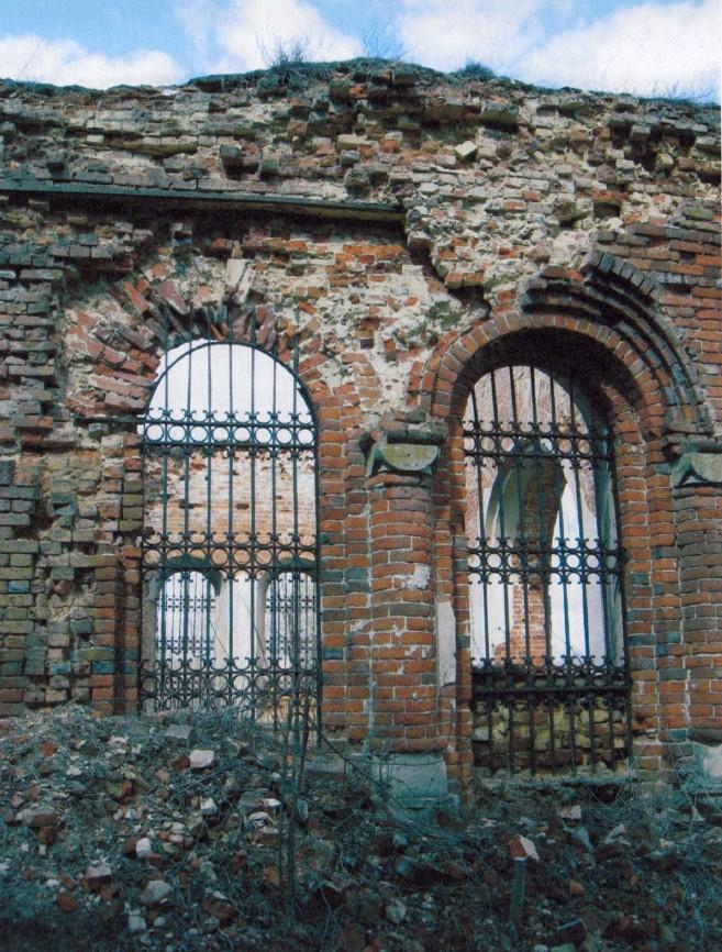 Южный фасад. Восточные спаренные окна. Полностью разрушена кладка верхней части стены, обнажившая внутреннюю связь. Утрачен декор.
