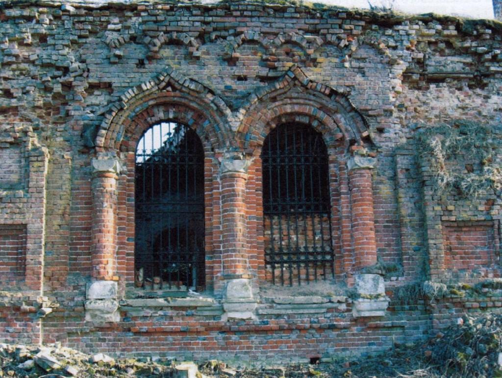Фрагмент северного фасада. Центральные спаренные окна. Разрушена верхняя часть кладки стены и лицевой кладки на лопатке.